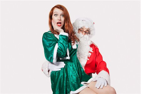 Portrait of Santa touching woman inappropriately against gray background Stock Photo - Premium Royalty-Free, Code: 693-06435904