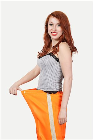 slim - Portrait of young Caucasian woman oversized orange pants against gray background Stock Photo - Premium Royalty-Free, Code: 693-06435935