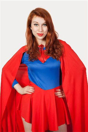 superhero costume - Portrait of young woman in superhero costume with hands on hips against gray background Stock Photo - Premium Royalty-Free, Code: 693-06435932