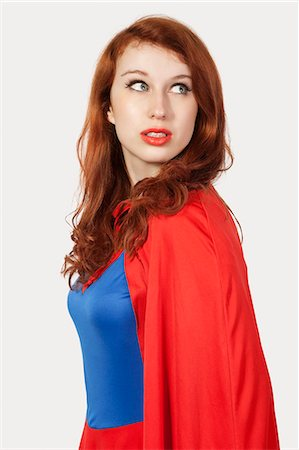 Young woman in superhero costume looking away against gray background Stock Photo - Premium Royalty-Free, Code: 693-06435933