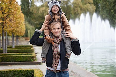 Portrait of father carrying son on his shoulders at park Stock Photo - Premium Royalty-Free, Code: 693-06435949