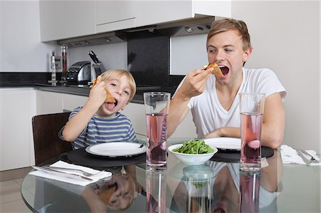 Father and son eating pizza at breakfast table Stock Photo - Premium Royalty-Free, Code: 693-06435988