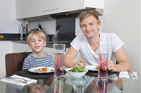 Portrait of father and son smiling at breakfast table Stock Photo - Premium Royalty-Free, Code: 693-06435989
