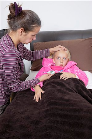 Mother checking unwell girl's temperature at home Stock Photo - Premium Royalty-Free, Code: 693-06435993