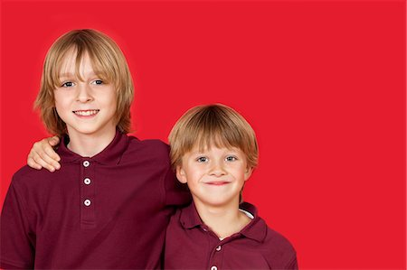 Portrait of two happy brothers against red background Stock Photo - Premium Royalty-Free, Code: 693-06436025