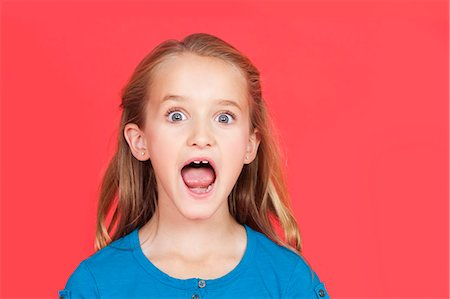 surprised - Portrait of shocked young girl with mouth open against red background Stock Photo - Premium Royalty-Free, Code: 693-06436040