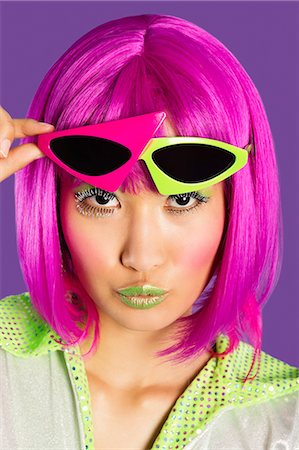 funky - Portrait of young funky woman in pink wig puckering lips over purple background Stock Photo - Premium Royalty-Free, Code: 693-06436067