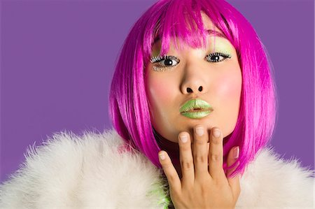 Portrait of young funky woman in pink wig blowing kiss over purple background Stock Photo - Premium Royalty-Free, Code: 693-06436063