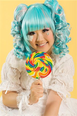 Portrait of smiling young woman dressed as a doll holding lollipop over yellow background Stock Photo - Premium Royalty-Free, Code: 693-06436075