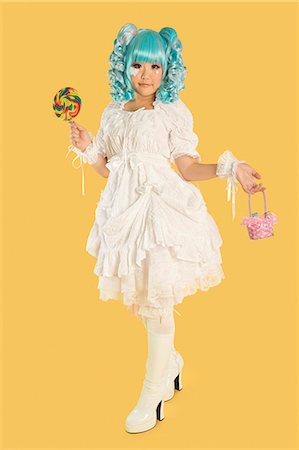 Full length portrait of young woman dressed as a doll holding lollipop over yellow background Stock Photo - Premium Royalty-Free, Code: 693-06436076