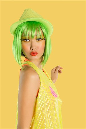 pucker - Portrait of funky young woman with green hair puckering her lips against yellow background Stock Photo - Premium Royalty-Free, Code: 693-06436079