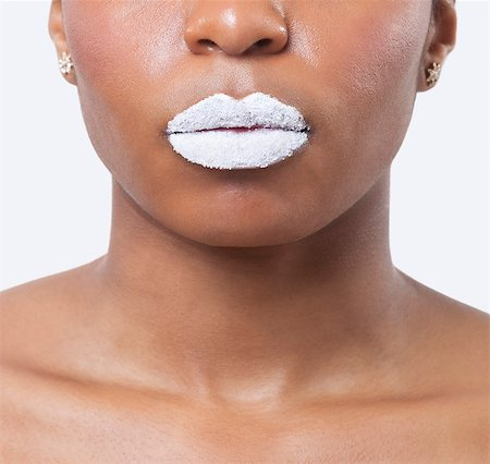 Close-up shot of young African American woman with white lips over white background Stock Photo - Premium Royalty-Free, Code: 693-06497574