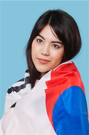 filipino ethnicity - Patriotic young woman wrapped in Korean flag over blue background Stock Photo - Premium Royalty-Free, Code: 693-06497570