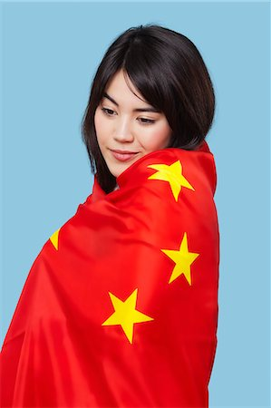 Patriotic young woman wrapped in Chinese flag over blue background Stock Photo - Premium Royalty-Free, Code: 693-06497571