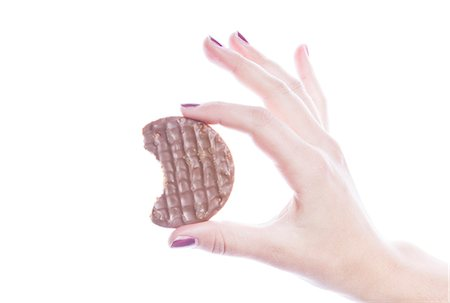 Detail shot of woman holding cookie over white background Stock Photo - Premium Royalty-Free, Code: 693-06497612