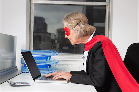 superhero costume - Side view of senior businesswoman in superhero costume using laptop at office desk Stock Photo - Premium Royalty-Free, Code: 693-06497646
