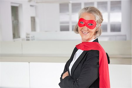 superhero - Portrait of smiling senior businesswoman in superhero costume in office Stock Photo - Premium Royalty-Free, Code: 693-06497648