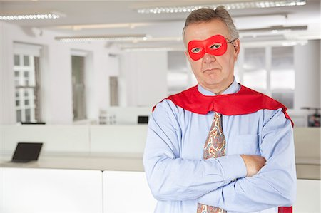 superhero - Portrait of serious businessman in superhero costume in office Stock Photo - Premium Royalty-Free, Code: 693-06497653