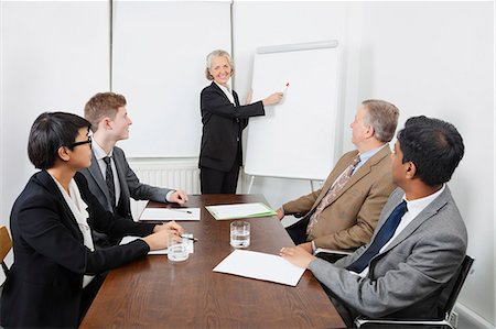 Senior woman using whiteboard in business meeting Stock Photo - Premium Royalty-Free, Code: 693-06497665