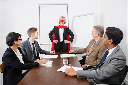 superhero costume - Business leader as superhero in front of colleagues at meeting in conference room Stock Photo - Premium Royalty-Free, Code: 693-06497667