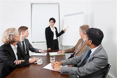 Young woman using whiteboard in business meeting Stock Photo - Premium Royalty-Free, Code: 693-06497669