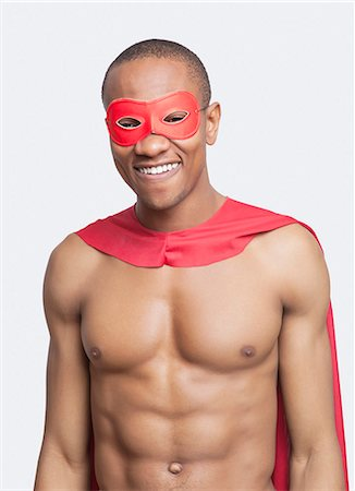Portrait of young shirtless man in superhero costume smiling against gray background Stock Photo - Premium Royalty-Free, Code: 693-06667802