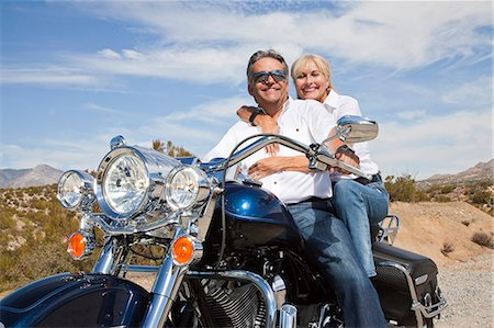 Senior couple on desert road sitting on motorcycle looking at camera Stock Photo - Premium Royalty-Free, Code: 693-06667816