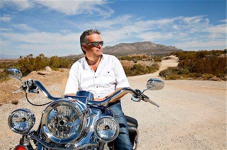 Senior man wearing sunglasses on motorcycle in desert Stock Photo - Premium Royalty-Free, Code: 693-06667818