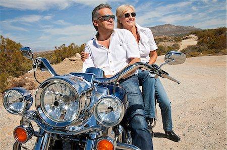 Senior couple wear sunglasses seated on motorcycle on desert road Stock Photo - Premium Royalty-Free, Code: 693-06667819