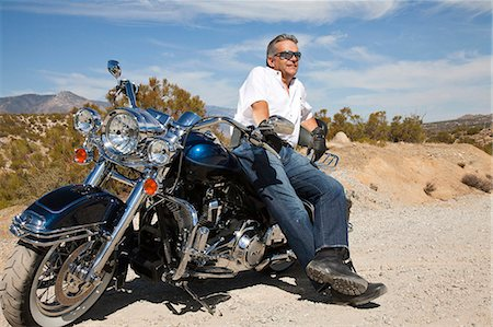 Senior man leaning on motorcycle on desert road Stock Photo - Premium Royalty-Free, Code: 693-06667820