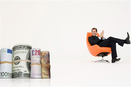 Happy businessman looking at money rolls representing growth in international business Stock Photo - Premium Royalty-Free, Code: 693-06667992
