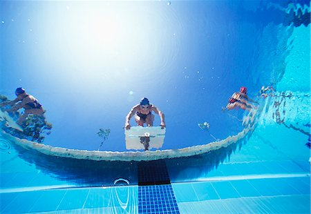 swimming pool water - Low angle view of female swimmers ready to dive in pool from starting position Stock Photo - Premium Royalty-Free, Code: 693-06668085