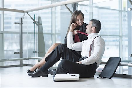 flirting - Businesswoman pulls male coworker towards her with his tie Stock Photo - Premium Royalty-Free, Code: 693-06967348