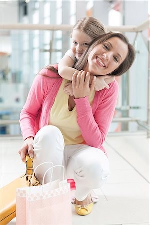 people on mall - Young daughter hugs mother in shopping mall Stock Photo - Premium Royalty-Free, Code: 693-06967364