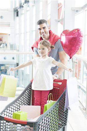shopping mall - Father pushing young daughter in shopping trolley with shopping bags Stock Photo - Premium Royalty-Free, Code: 693-06967367