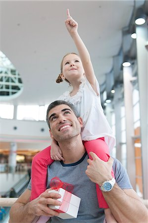 shopping mall - Young daughter points and sits on fathers shoulders Stock Photo - Premium Royalty-Free, Code: 693-06967375