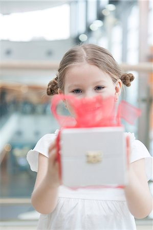 Young girl handing present towards camera Stock Photo - Premium Royalty-Free, Code: 693-06967377