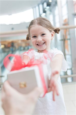present wrapped close up - Young girl being giving a present Stock Photo - Premium Royalty-Free, Code: 693-06967378