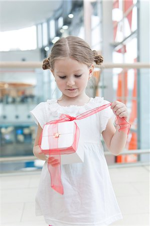 present wrapped close up - Young girl unwrapping ribbon on present Stock Photo - Premium Royalty-Free, Code: 693-06967379
