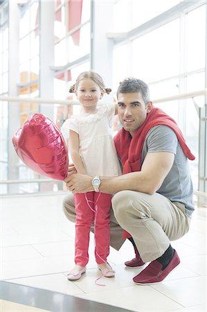 shopping mall - Father kneels with younger daughter holding balloon Stock Photo - Premium Royalty-Free, Code: 693-06967372