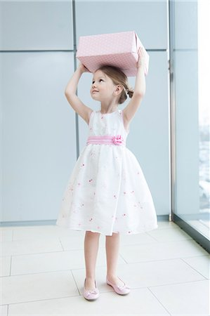 shopping mall - Young girl holding gift wrapped box on her head Stock Photo - Premium Royalty-Free, Code: 693-06967385
