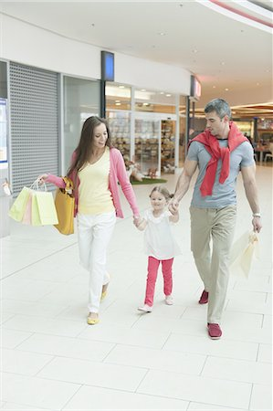shopping mall - Young girl holding parents hands in shopping mall Stock Photo - Premium Royalty-Free, Code: 693-06967406