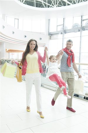 shopping mall - Young girl holding hands and swinging between mother and father Stock Photo - Premium Royalty-Free, Code: 693-06967408