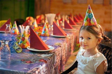 Young girl seated at her birthday table Stock Photo - Premium Royalty-Free, Code: 693-06967400