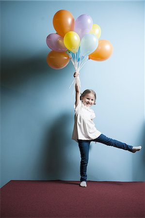 fly - Young girl pretending to be lifted up by bunch of balloons Stock Photo - Premium Royalty-Free, Code: 693-06967402