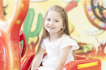 red - Young girl sitting on childrens car ride Stock Photo - Premium Royalty-Free, Code: 693-06967403