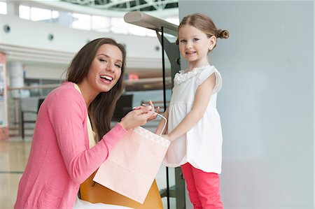 shopping mall - Mother giving daughter paper shopping bag Stock Photo - Premium Royalty-Free, Code: 693-06967417