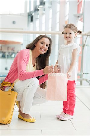 shopping mall - Mother giving daughter paper shopping bag Stock Photo - Premium Royalty-Free, Code: 693-06967418