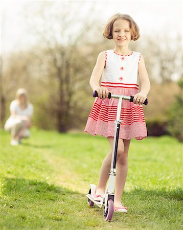 elementary age - Young girl riding scooter through park with mother in background Stock Photo - Premium Royalty-Free, Code: 693-06967424