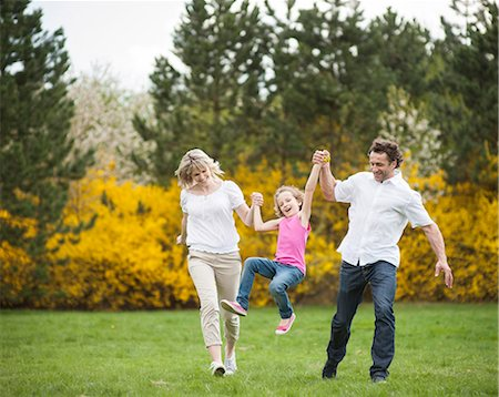 swing (sports) - Young couple swinging daughter between them Stock Photo - Premium Royalty-Free, Code: 693-06967440